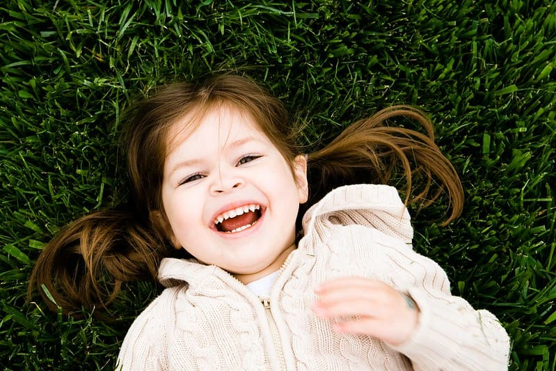 Little girl lying down in the grass laughing at pig jokes.