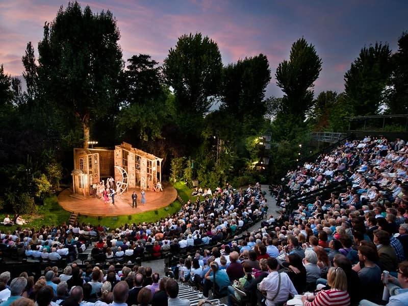 Audience at Regent's Park Open Air Theatre at dusk.