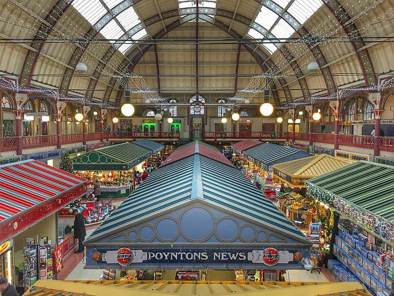 Inside Derby market at Christmas time with fairy light decorating all the stalls.