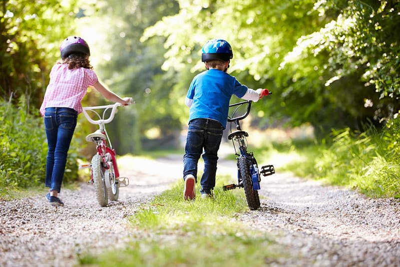 Little girl and boy pushing their bikes along the path on a nature trail.