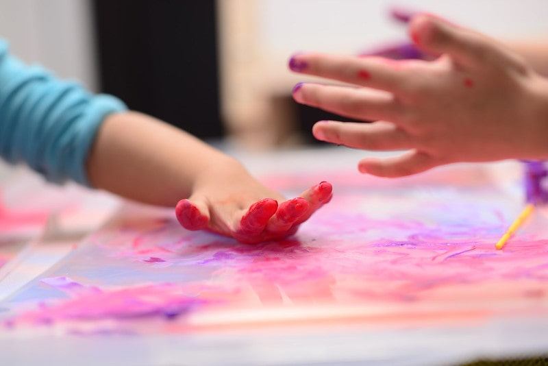 Kids' finger painting activity, a close up of their hands covered in red paint.