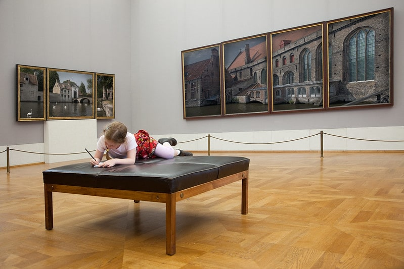 Little girl lying on a seat in a museum drawing in her notebook.