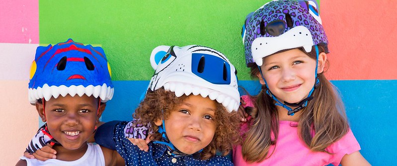 Three children wearing Crazy Safety Kids Bike Helmet shaped like a dinosaur, a cat and a bear.