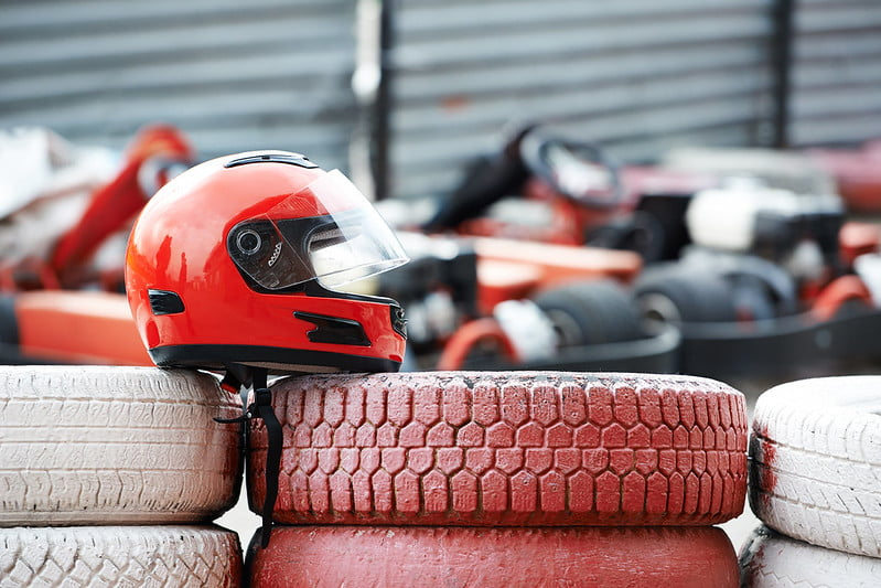 A red helmet on top of a stack of red tyres at the go karting track.