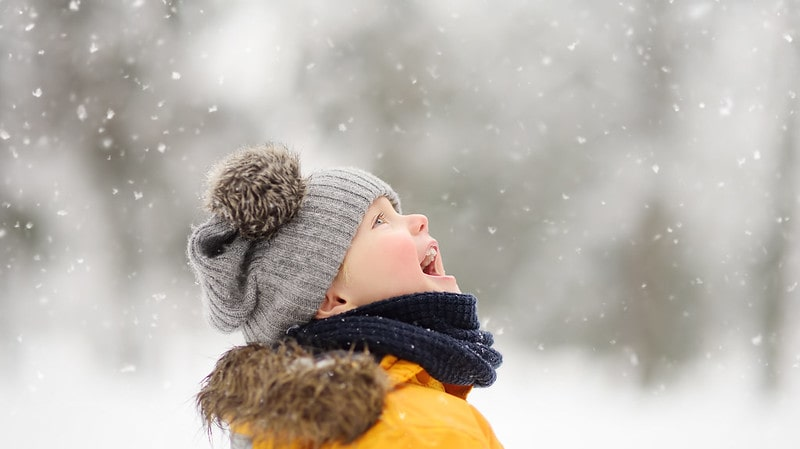 Little boy wrapped up wearing a grey woolly hat outside laughing as the snow falls.