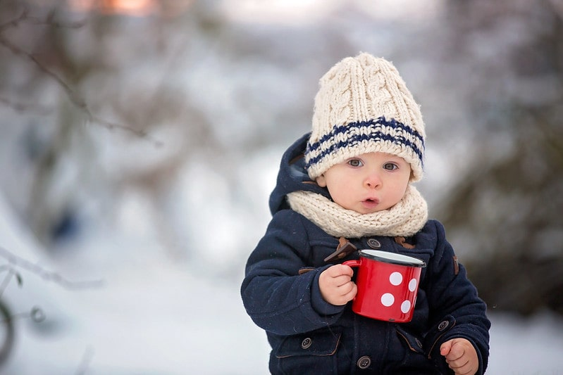 Baby boy wrapped up wearing a woolly hat, sat outside in the snow holding a mug.