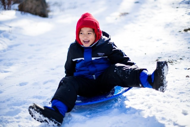 Young boy on a toboggan smiling as he slides down the hill on the snow.