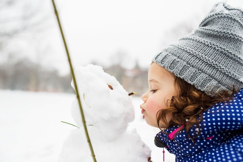 Little girl wearing a grey woolly hat, standing outside kissing a snowman.