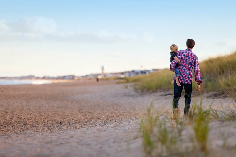 Dad carrying his young son in his arms as he walks along the beach in Sunderland.