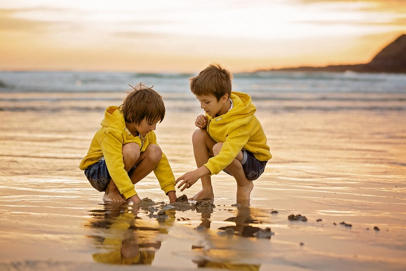 Two young boys wearing matching yellow hoodies, crouching down to play with the sand on the beach.
