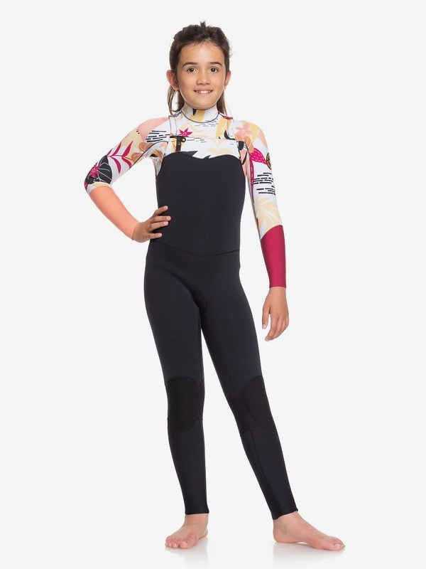 A young girl modelling the 3/2mm POP Surf Wetsuit, with fun patterns.