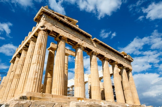 The Parthenon in Athens, Greece, on a sunny day with blue skies behind.
