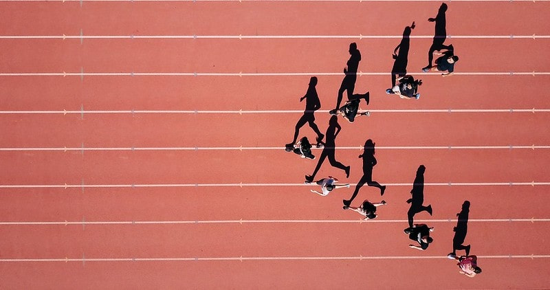 Runners on an athletics track, on a sunny day, their shadows on the track.