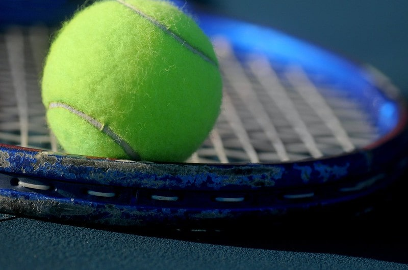 Close up of a tennis ball on the strings of a blue tennis racquet.y