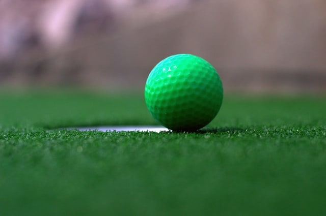 Close up of a green golf ball on the edge of the hole on the golf course.