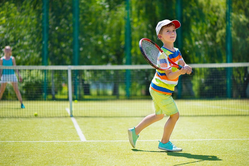 Young boy in a colourful striped t shirt and cap playing tennis.