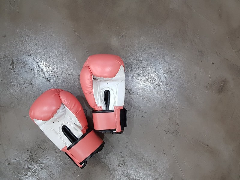 Pair of pink and white boxing gloves on the floor in the training studio.
