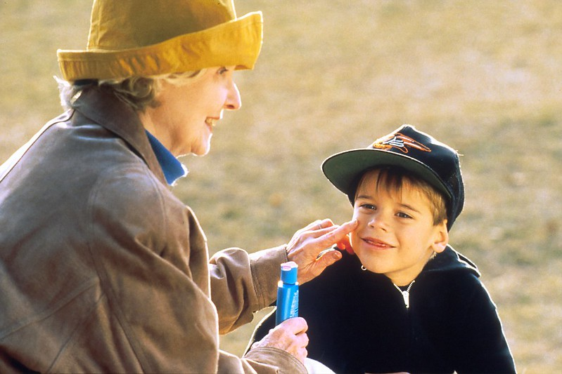 grandma putting sun cream on little boy