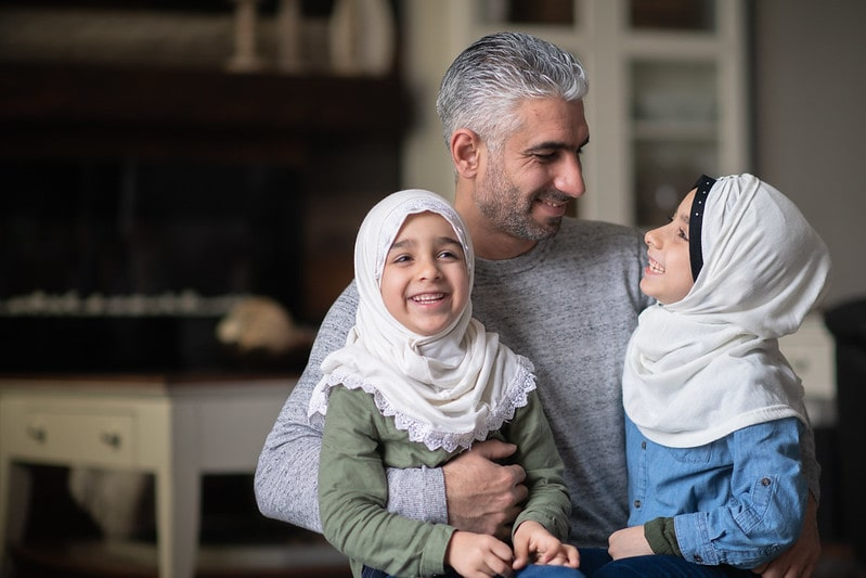 Two young girls wearing headscarves sat on their dad's lap happy and smiling.