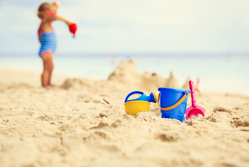 girl building sandcastles on the beach with her sand toys