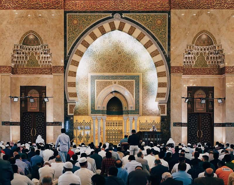 Inside an ornately decorated mosque, men are doing Ramadan prayers.