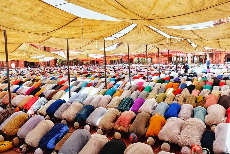 Rows of men bent over, bowing their heads in prayer at the mosque.
