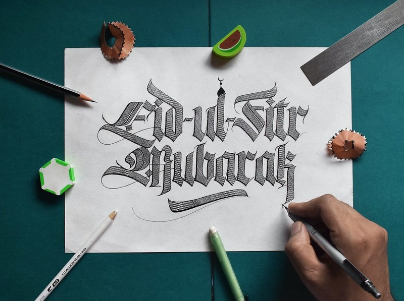 Happy Eid sign written on paper in caligraphy.