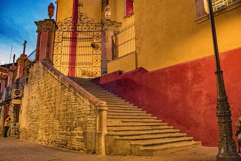 Colourful architecture in Mexico City: a staircase leading up to a gate of a red and yellow building.