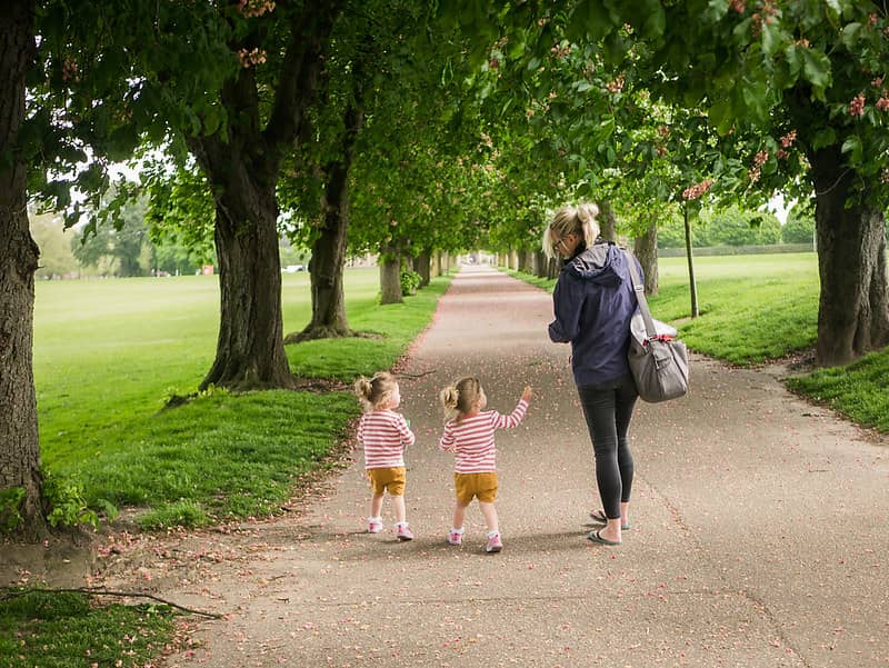 Little twins walking in the park with their mum under a tree-lined path on a day out in Chelmsford.