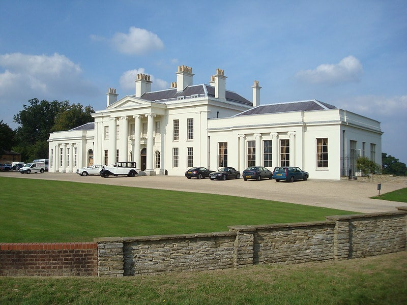A front view of the Hylands Estate park house, a cream exterior with columns outside the front door.