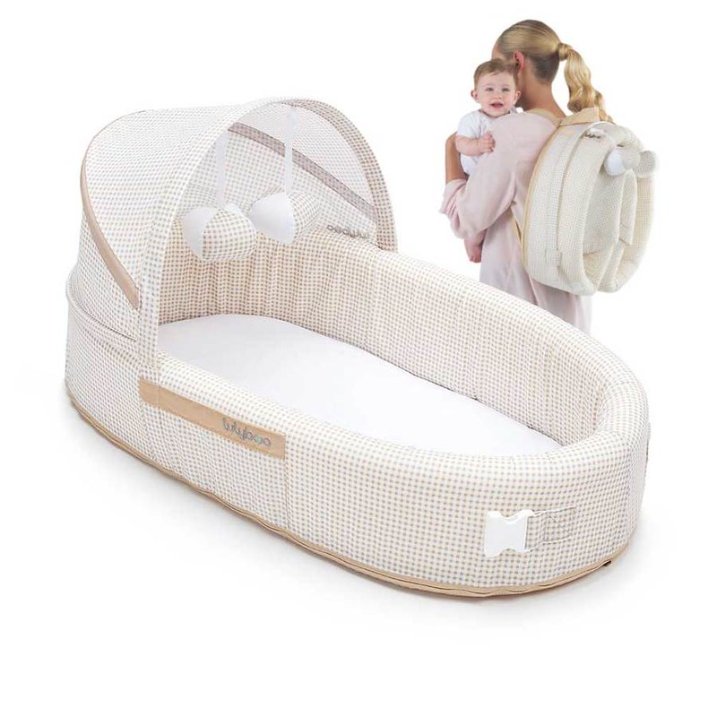 Mum carrying the baby and the Lulyboo Baby Lounge To Go Travel Bed.