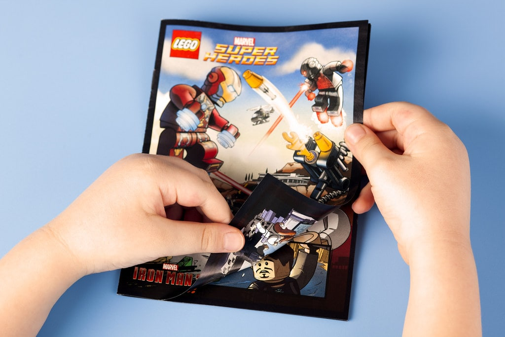 A child's hands opening a Lego Marvel Superheroes comic book.