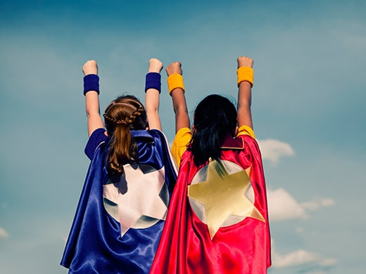 Two young girls dressed in Captain Marvel costumes pretending to fly away.
