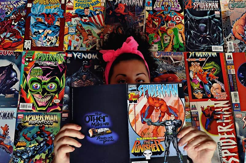 Girl standing in front of rows of Marvel comic books holding a Spiderman comic open in front of her face.