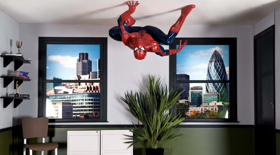 A model of Marvel's Spiderman crouching on the ceiling of a London office.