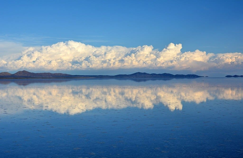 Bolivian landscape skyline mirrored in the lake, hills with a cloudy blue sky above.