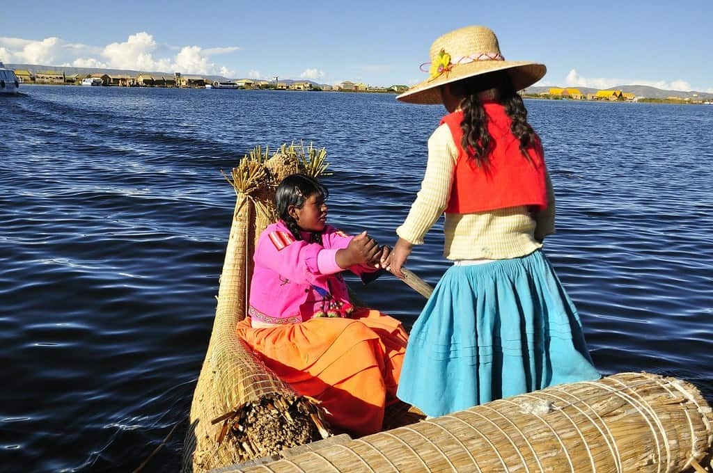 Two Bolivian girls on a reed boat crossing lake Titicaca.
