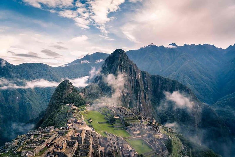 A view from above of Machu Picchu with the sun setting behind.