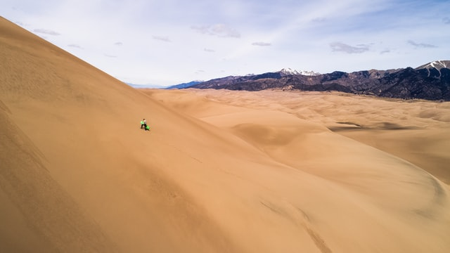 Man climbing up a large sand dune in Peru, mountains visible at the edge of the sand.