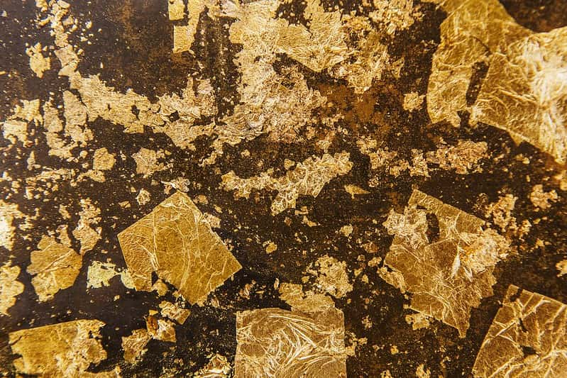 Squares of gold crushed against a brown surface.