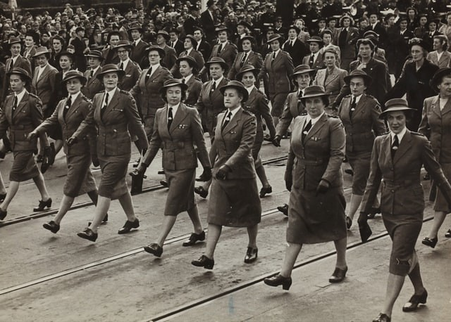 A black and white picture of many women in uniform marching for VE day.