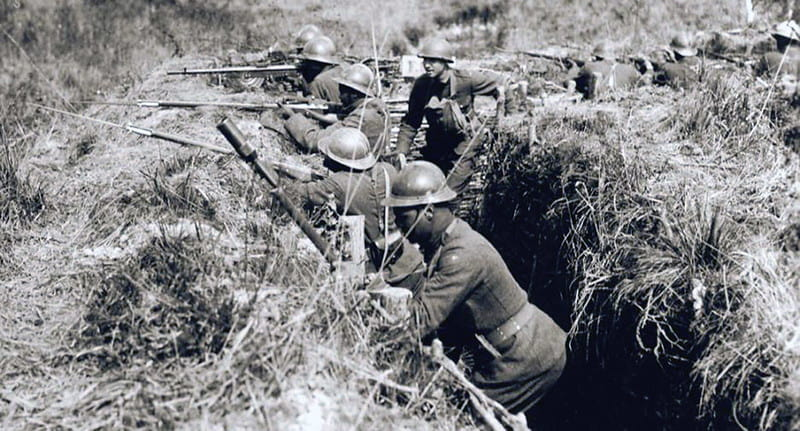 A black and white photo of soldiers in trenches aiming their guns.s