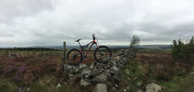 A bike on a rock wall in the countryside at Kirkhill Forest.