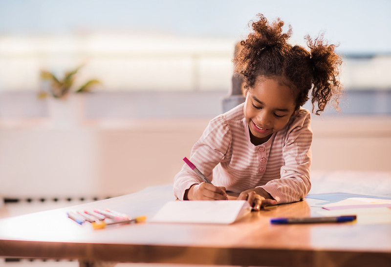 Girl relaxing on the table at home and coloring in notebook