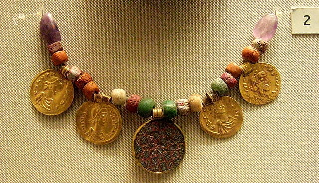 An Anglo-Saxon necklace, made from beads and large gold coins, hanging on display in a museum.