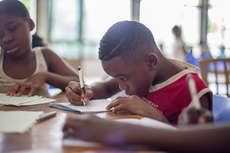 Young boy at his desk in school writing out improper fractions in workbook.