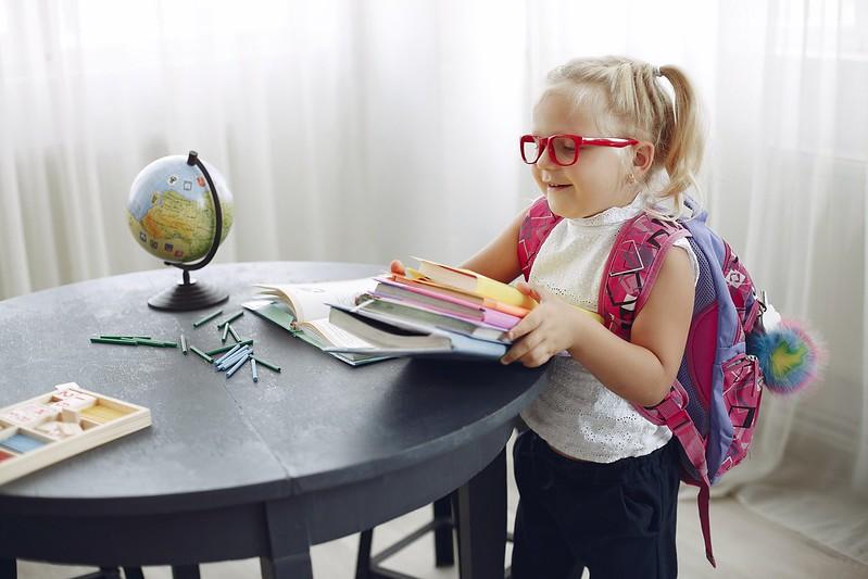 Girl wearing backpack taking her books