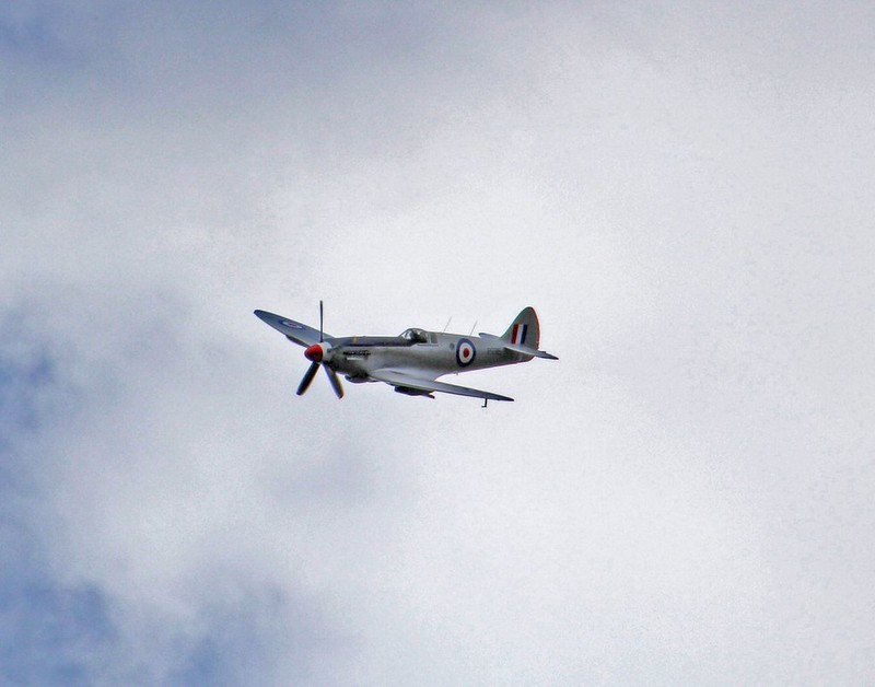 WW2 RAF fighter plane flying through the sky.