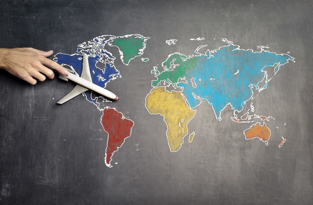 Map of the world drawn on a blackboard, the teacher moves a toy plane across it.