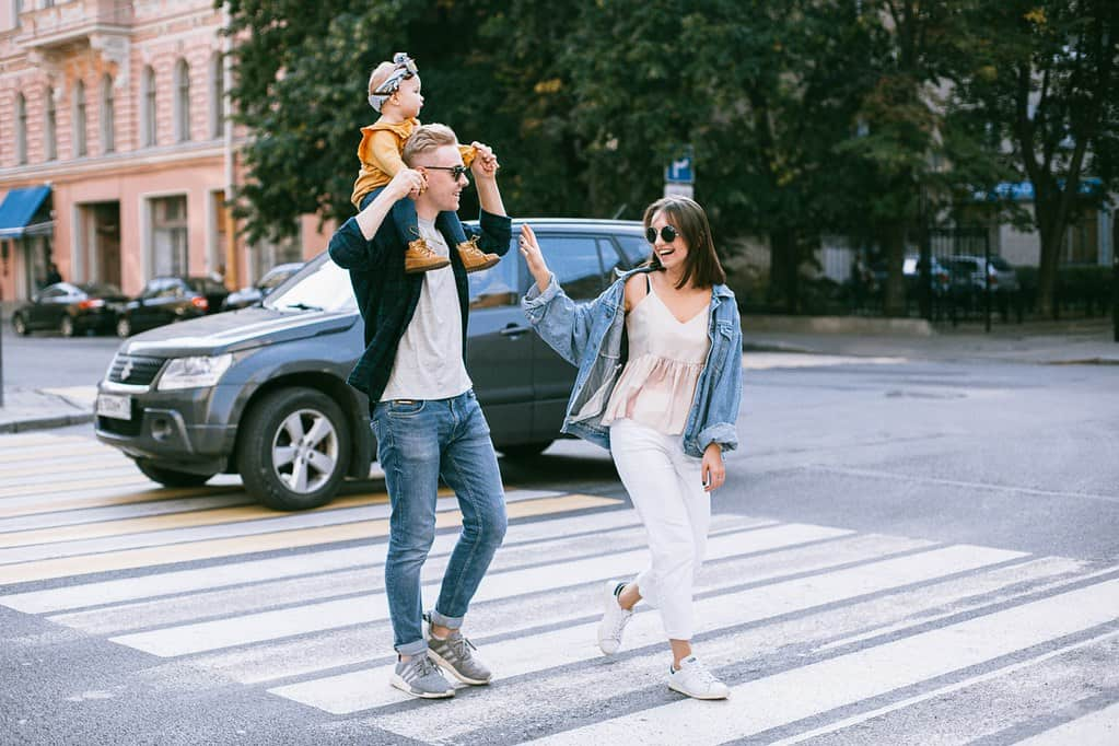 Parents crossing the road with their baby girl on her dad's shoulders.